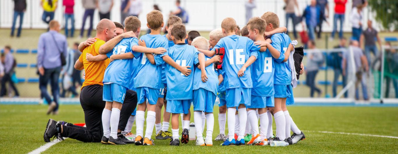 jonge voetballers steken de koppen bij elkaar