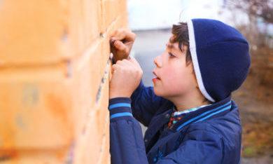kind schrijft op de muur