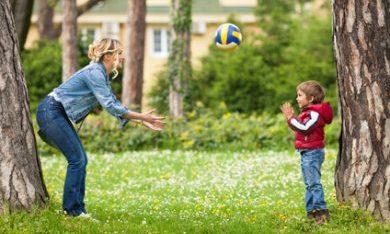 moeder en zoon spelen buiten met de bal